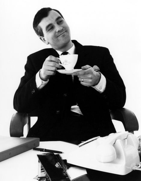 A man sits back from his desk to enjoy a cup of tea. Date: late 1960s