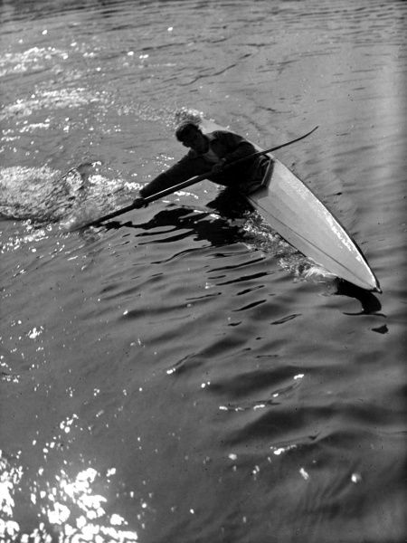 Slicing through glistening waters in a canoe! Date: 1930s