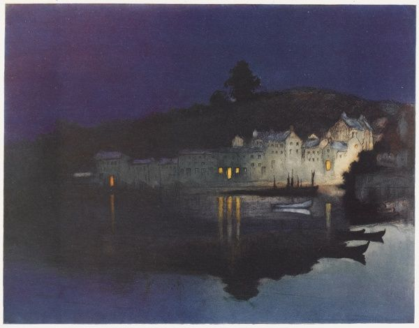 A night time scene showing dwellings and boats dimly lit on the River Dart above an inky blue sky