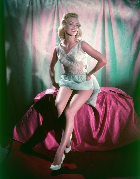 A blonde woman reveas her long legs as she poses for the camers wearing a white nightdress Date: 1950s