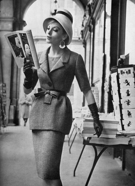 A model studies a fashion magazine while wearing a dress in flecked grey wool with a peplum overskirt giving a fashionable tiered effect by Nina Ricci, worn with a short bolero jacket. Date: 1960