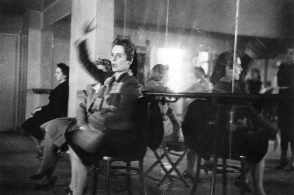 Ninette de Valois sitting on a chair with her back to a large mirror, presiding over a ballet class or rehearsal