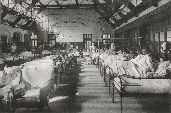 Staff and patients in Ward A13 at the No. 2 War Hospital, Reading, Berkshire - the First World War deployment of Battle School, Cranbury Road, Reading. The far wall bears the school motto 'Fight the Good Fight&#39