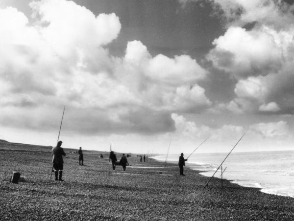 Sea anglers fishing from a pebble beach near Sheringham, Norfolk, England. Date: 1950s