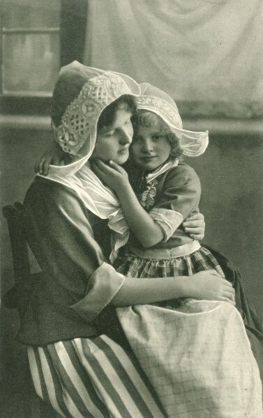 Picture postcard showing a young Normandy woman in traditional dress, embracing a child in similar costume