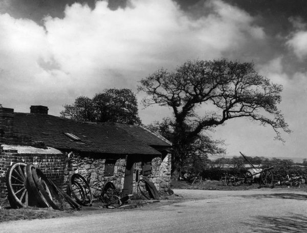 A picturesque old smithy (blacksmith's shop) at Northop, Flintshire, Wales. Date: 1930s
