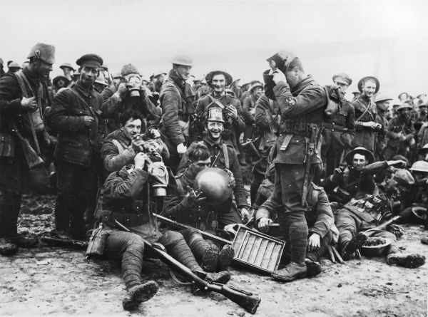 Northumberland Fusiliers wearing German helmets and gas masks captured during the fighting at St Eloi, near Ypres, on 27th March 1916. Earlier that day six mines had been exploded under German positions