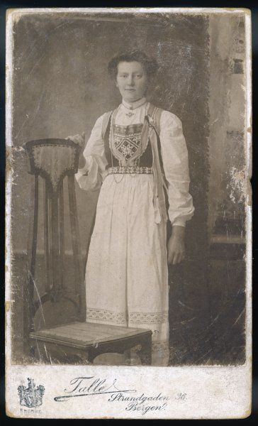 A young woman poses for a studio photograph wearing her regional costume. She stands next to an unusual Art Nouveau style chair