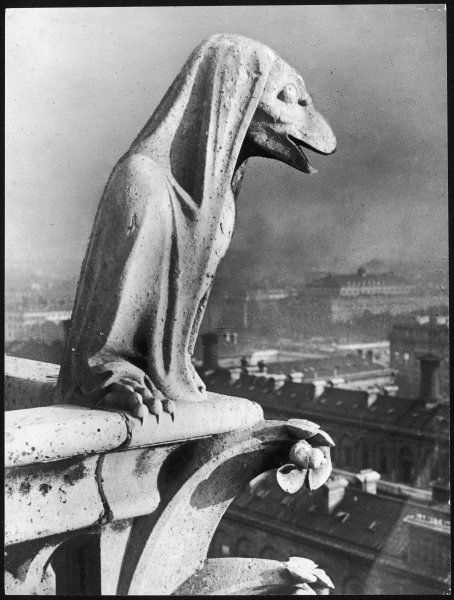 A gargoyle looks down over Paris from Notre Dame cathedral