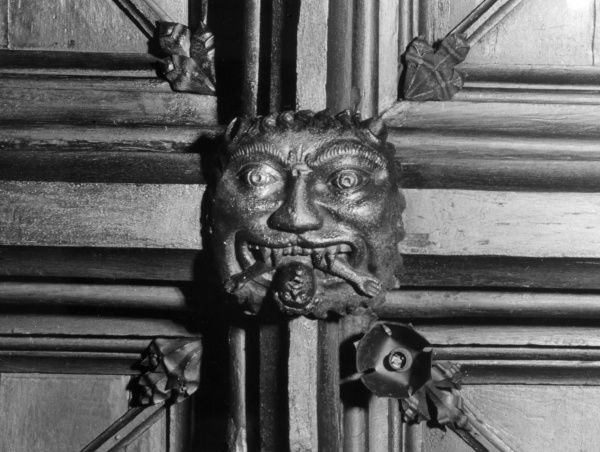 A medieval carving, on a ceiling in the Audit Room at Chetham's Hospital, Manchester, England, of the legendary Notting Hill Giant, eating a poor boy. Date: Medieval