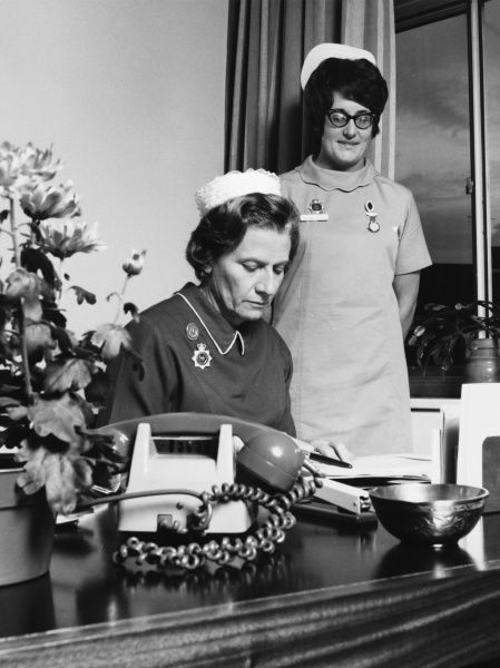 Scene at the Metropolitan Police Medical Centre, Hendon, north west London, showing a matron sitting at her desk while a nurse stands respectfully behind her