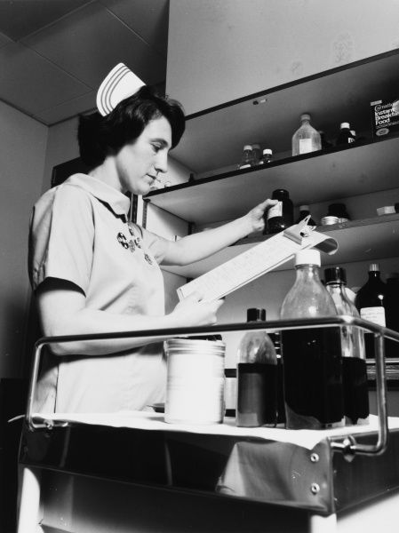 Scene at the Metropolitan Police Medical Centre, Hendon, north west London, with a nurse selecting medicines from a cupboard, while referring to a checklist on a clipboard
