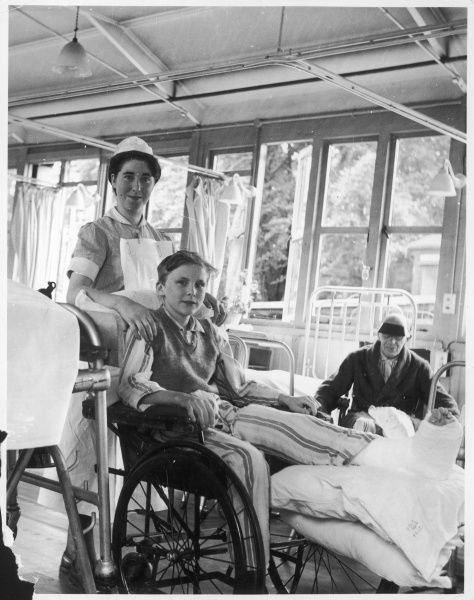 A cadet (student) nurse looks after a boy patient, (who has a broken leg in plaster), in a special wheelchair with a leg support. Queen Mary's Hospital Sidcup, Kent, England