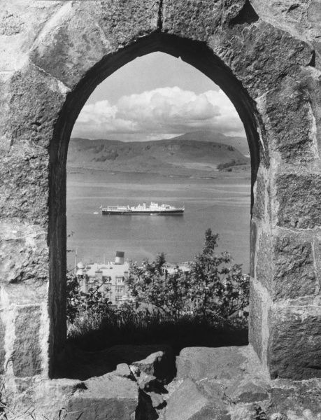 An archway of beauty, in the Scottish Western Highlands, looking over the harbour at Oban, Argyllshire, from McCaig's Tower to the Isle of Kerrara and mountains of Mull