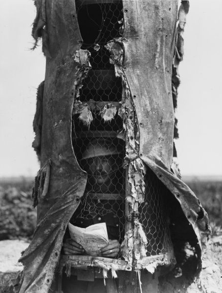 A soldier in a canvas and steel observation post near Souchez on the Western Front in France during World War I in May 1918