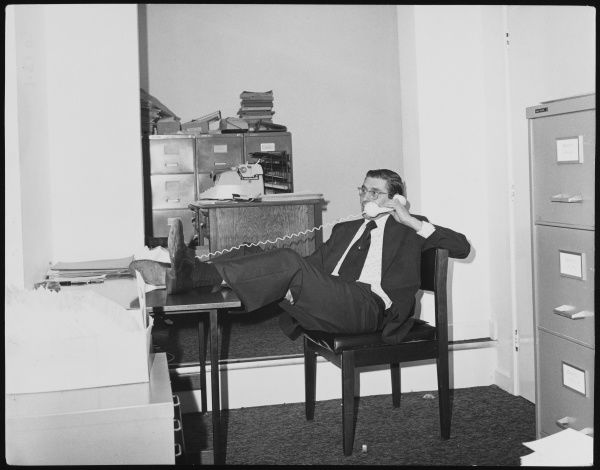 A businessman in a suit takes a phone call with his feet up on his desk