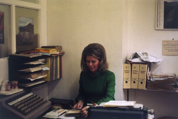 A female office worker, sitting at her desk, surrounded by box files and in trays, her typewriter beside her. Date: 1975