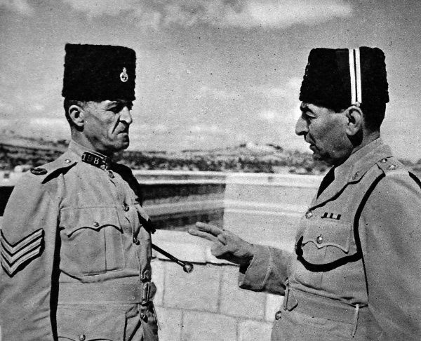 Photograph showing an Arab Drill Sergeant (on left) and Officer of the Palestine Police Force at their barracks in Jerusalem, November 1945