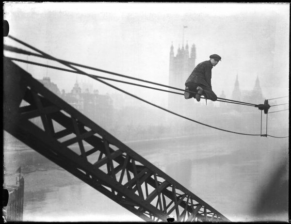 This brave workman risks his life to oil one of the pulleys used to construct the new Lambeth Bridge, designed by George Humphreys, opened by George V in 1932