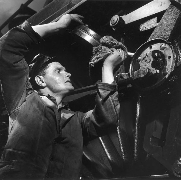 A railway engineer oils the end of a piston on an immense steam train wheel. Photograph by Heinz Zinram