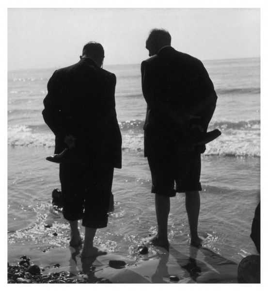 Two men paddling in the sea: they wear formal suits