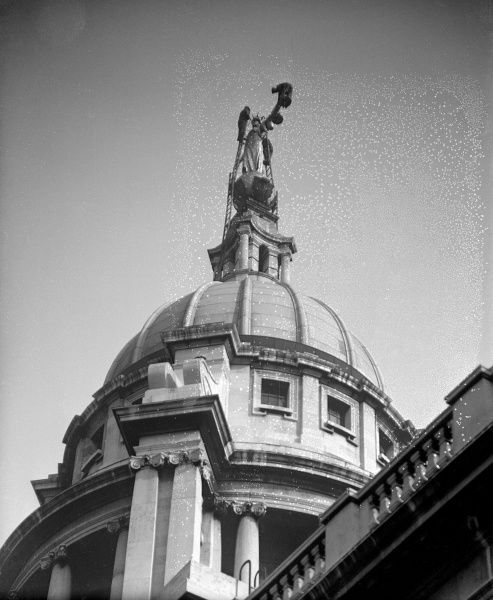 The dome of the Old Bailey, topped by the magnificent gold statue of Justice, holding a sword in one hand and weighing scales in the other. Date: early 1930s
