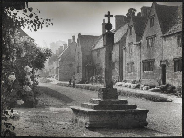 The Old Cross stands at the bottom of a picturesque street in Stanton Village, Cotswolds, Gloucestershire. Three children run up the street in the distance