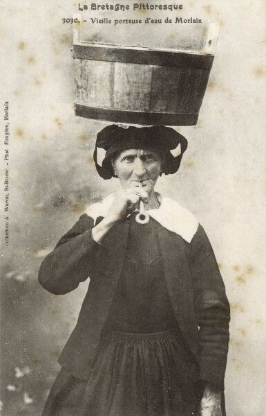 Old French Water Carrier from Morlaix, Brittany - smoking a pipe. Date: circa 1910s