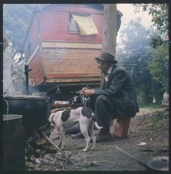 At an encampment in Surrey an old Gypsy man sits on a can close to the fire