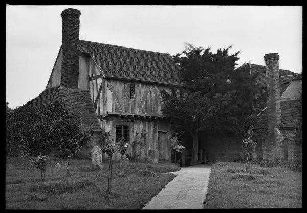 An old timbered house with a graveyard in the foreground