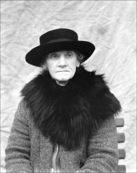 An old lady wearing a wide-brimmed hat and a coat with a large black fur collar