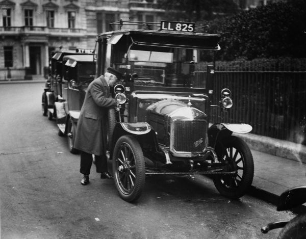 An old taxi cab driver with his 'older' style cab, at the front of a taxi rank in a London square. Date: 1931