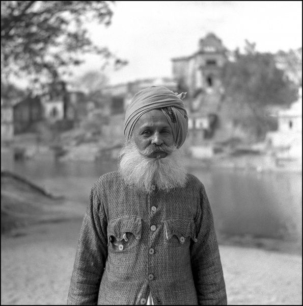 An old man poses for his photograph by the River Ganges at Varanasi (Benares), Uttar Pradesh, India. Photograph by Ralph Ponsonby Watts