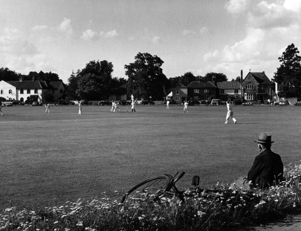 An old man sits on a grass verge with his upturned bicycle beside him and enjoys watching the cricket match on Giggs Hill Green, Thames Ditton, Surrey, England. Date: 1950s