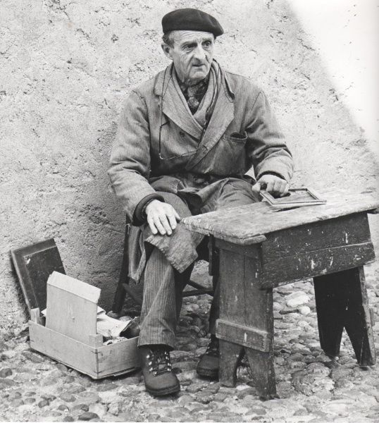An old man (possibly Spanish) working on the street. He wears a scruffy overcoat, a beret, and his glasses on a string round his neck. He has a small wooden work bench and a box of materials. Perhaps he is a picture framer