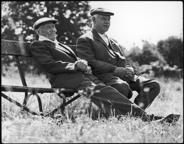 Two elderly men in cloth caps take a breather on a park bench