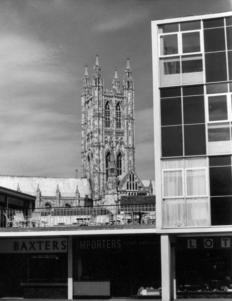 Old and new Canterbury, Kent, England - the Cathedral tower behind a row of 'modern' shops. Date: 1960s