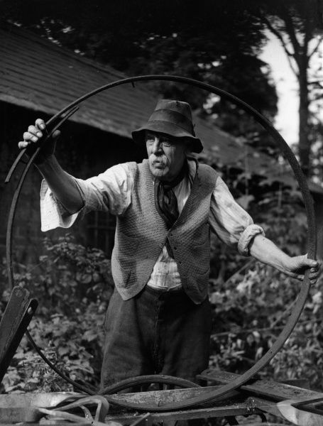An old wheelwright putting together a wheel in his yard, Surrey, England. Date: 1930s