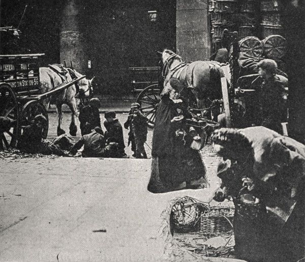Two old women scavenging for rotten vegetables amongst market garbage in the East End of London. The scene may have been artificially constructed by superimposing several separate images