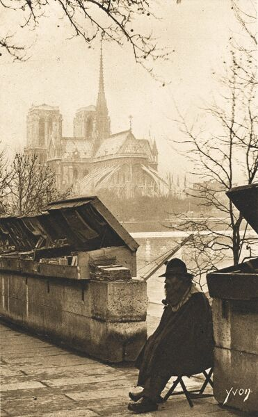 A wonderful photographic postcard showing the 'Oldest Book Dealer in Paris' - an old bearded man selling volumes from large wooden crates on the banks of the Seine, close to the Cathedral of Notre Dame, which looms large in the background