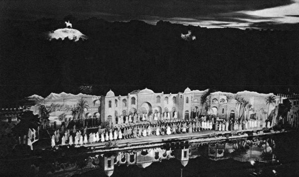 A night-time production of The Desert Song at the open air theatre in Scarborough, North Yorkshire. The full cast of the Scarborough Amateur Operatic Society appears to be on stage, and part of the set is reflected in the water. Date: 1952
