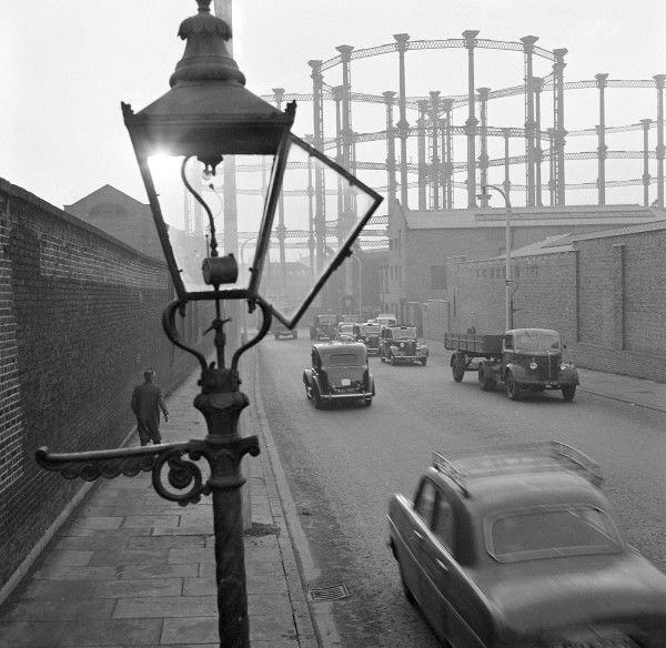 A street view with an open gas street light in the foreground, two high walls to either side of the road, a man walking, traffic on the road and the gasometers at Kings Cross in the distance imperial gas light and coke company gas holders, Camden Town