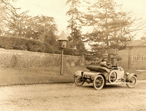A lady driving an open-top sports coupe past a dovecote