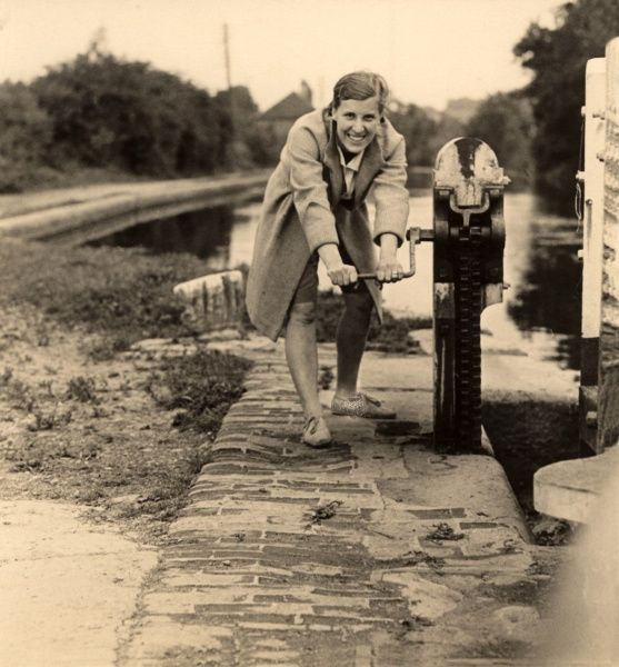 A smiling woman opens a lock on a canal at Brentford, Middlesex in 1930