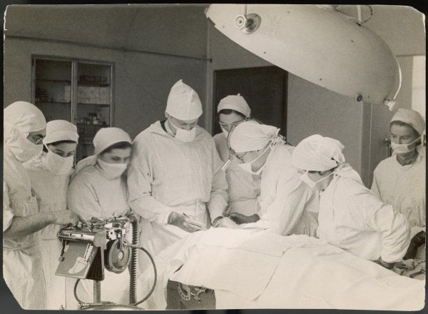 A group of student nurses in theatre, observing a surgeon performing an operation
