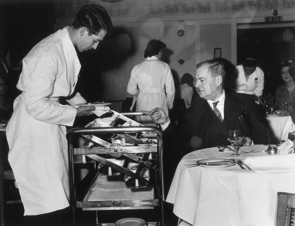 A man orders his food by choosing from a trolley in a hotel restaurant. Date: 1950s