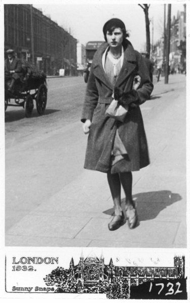 A young woman walking down a street in East Finchley, London wearing a beret, fur mittens, an overcoat and T- bar shoes and carrying her shopping in a paper bag