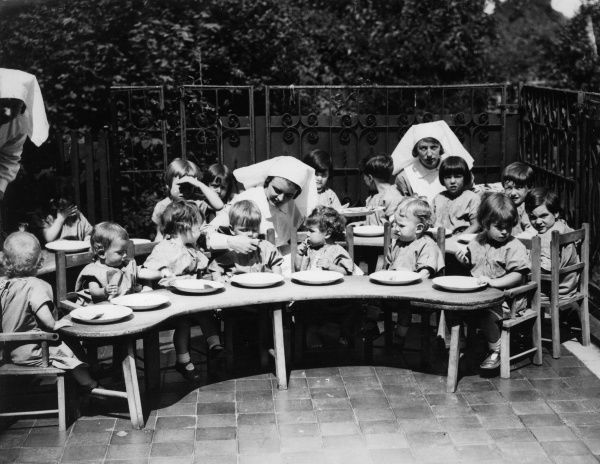 Staff feed the children at the Finchley Dispensary for orphans Date: 1930s