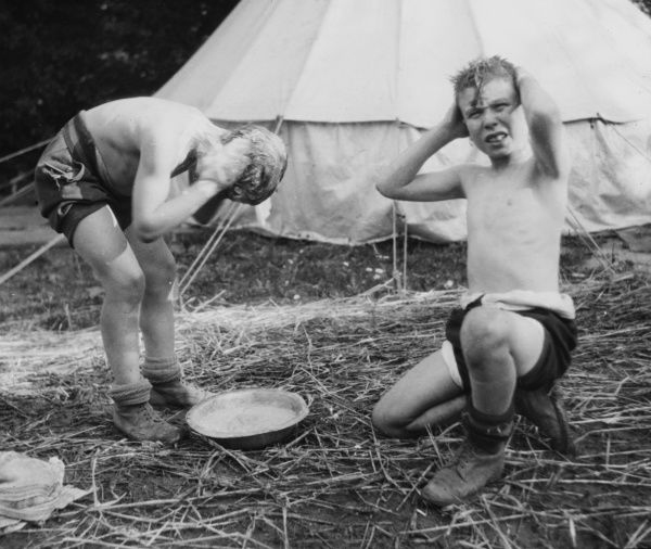 Two boys wash the grime from their hair using a small bowl of water outside of their tent