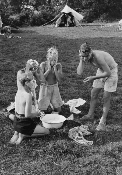 Four boys from a Boys Club wash outdoors using soap and a small bowl of water